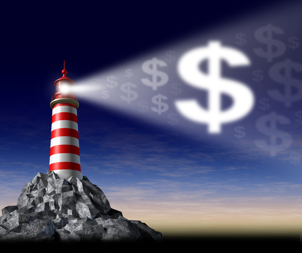 A lighthouse shines toward an illuminated Dollar sign against the sky