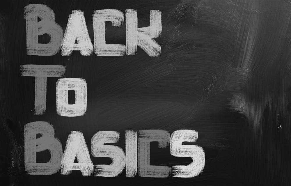 3 words, Back to Basics, are written in chalk on a blackboard