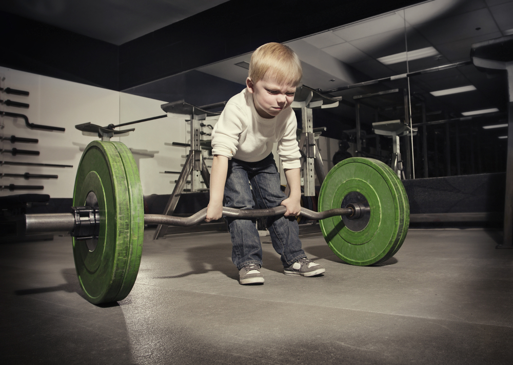 a young boy struggles to lift a heavy bar bell