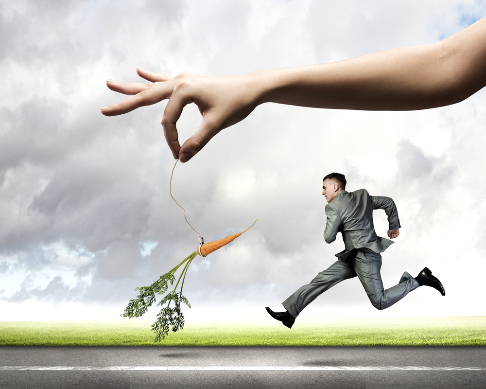 Solution Selling Compensation Strategies a business man is chasing a huge carrot dangled in front of him