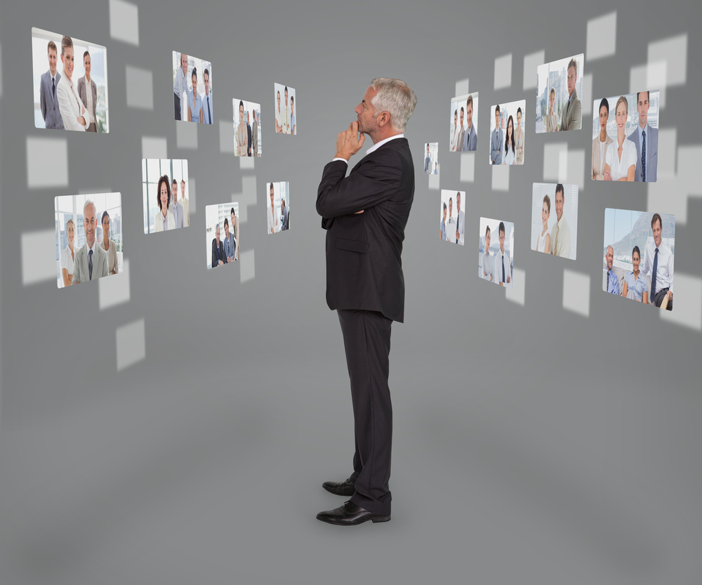 A business man is looking at many candidate photos on the wall