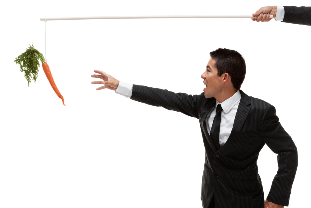 a businessman reaches for a carrot held on the end of a fishing pole