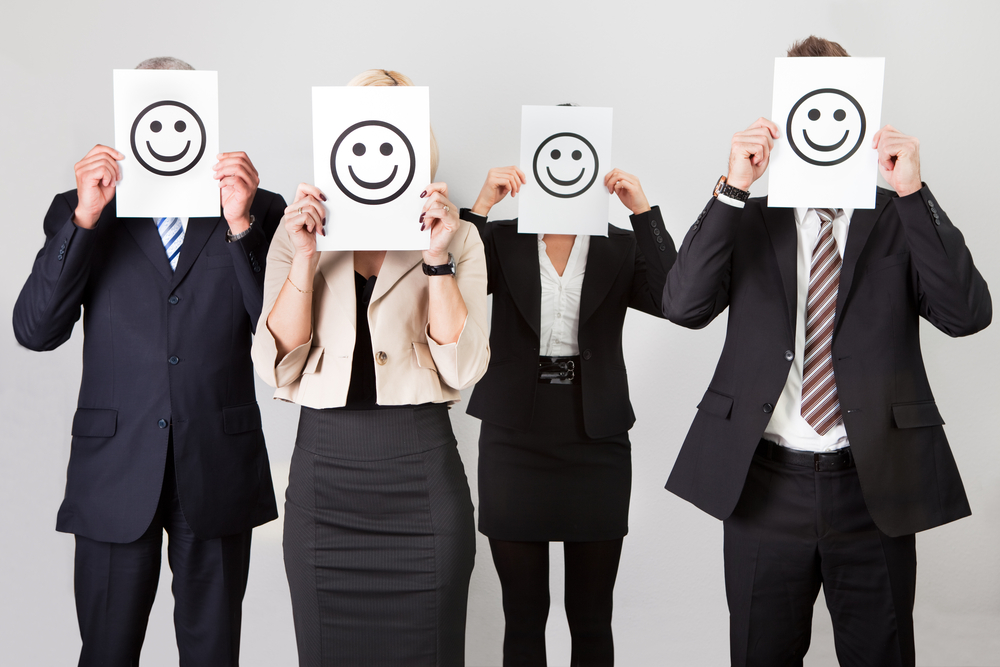 "4 business people cover their faces with ""smily face"" drawings"