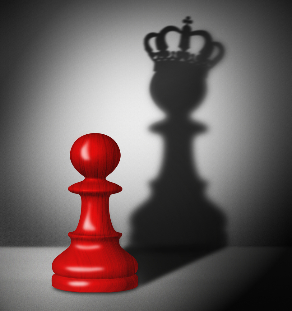 A pawn casts a shadow of a chessboard king