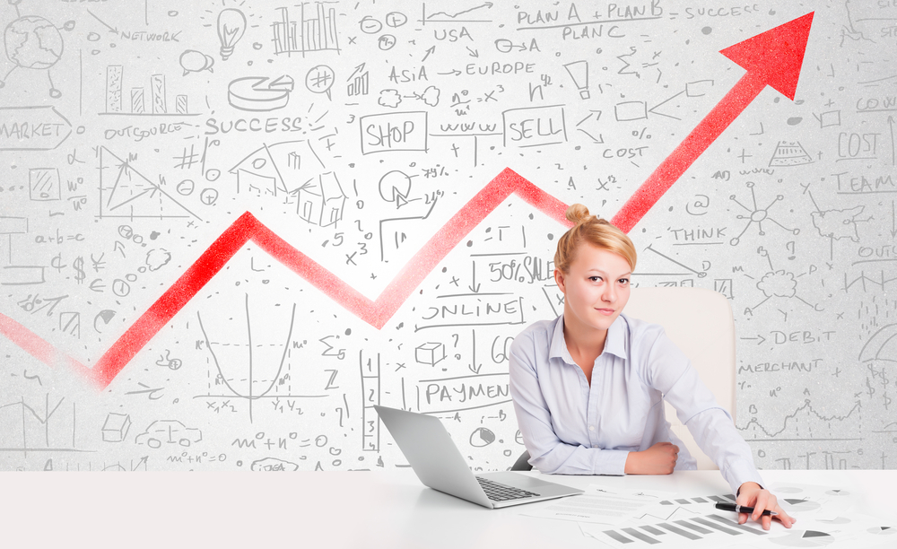 A woman is sitting in front of a graph of an upward pointing arrow