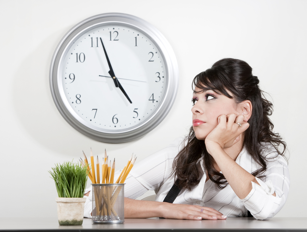 a young employee is bored and watches as the clock approaches 5...quitting time