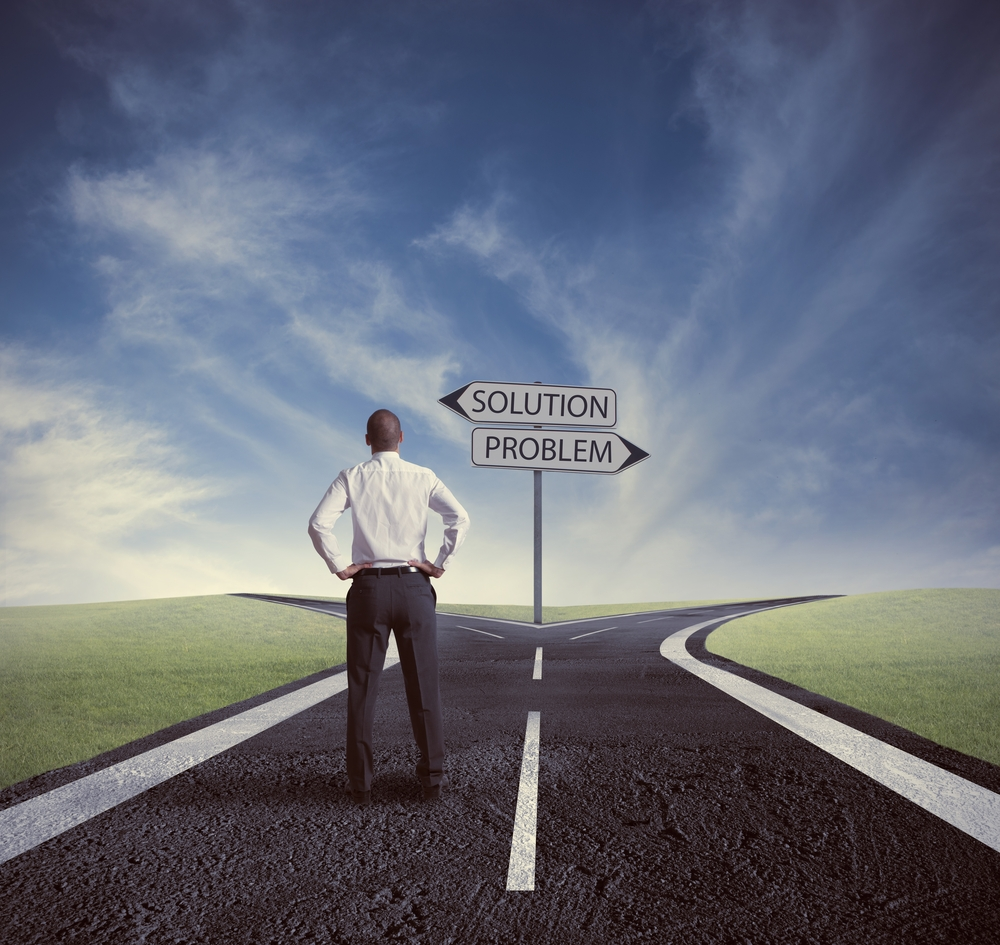 A man stands at a crossroads and must choose the problem or the solution path for better employee engagement