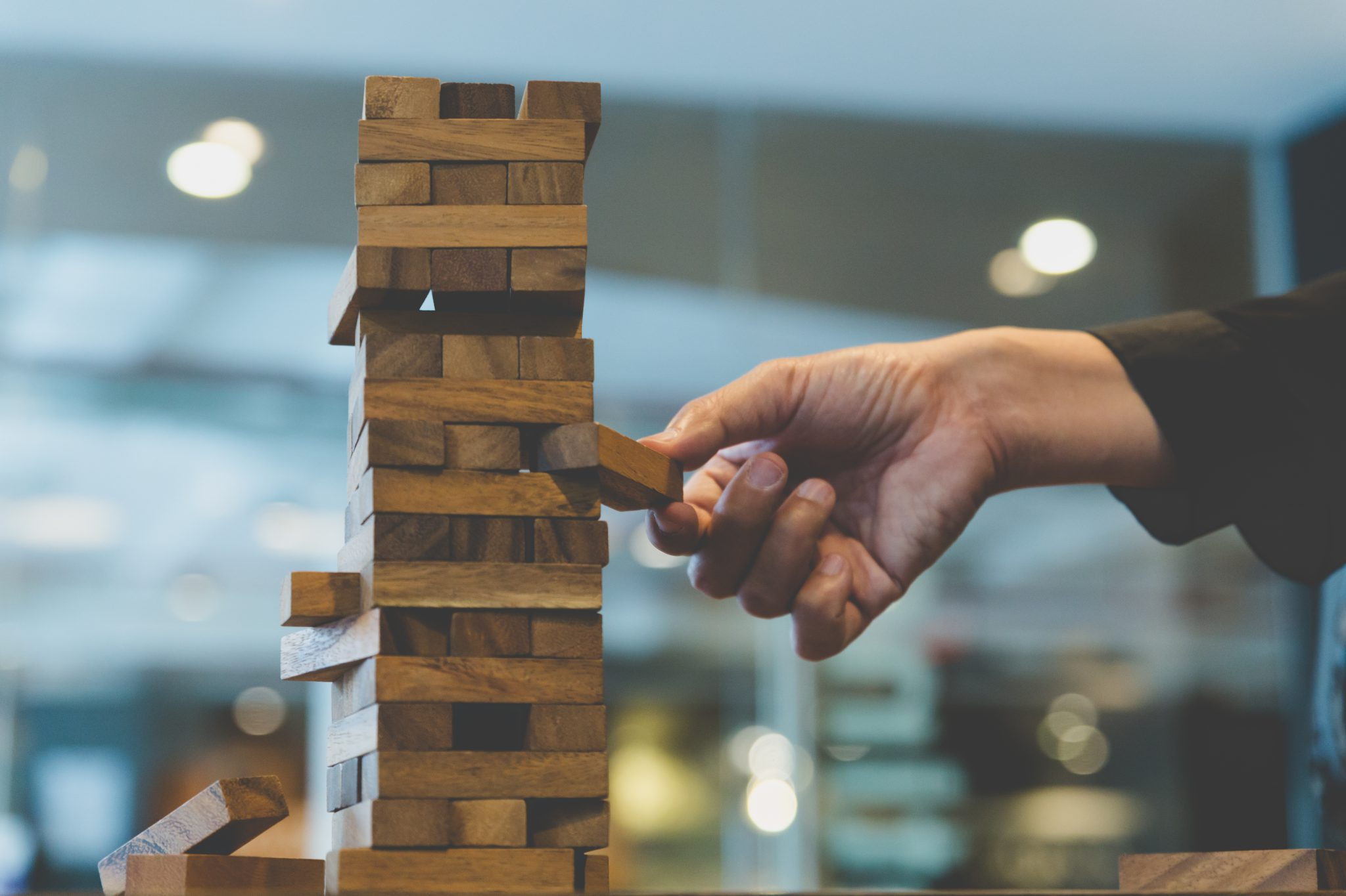 One hand is pulling out a block from a Jenga game tower to show how important strategic clarity is in the moves you make