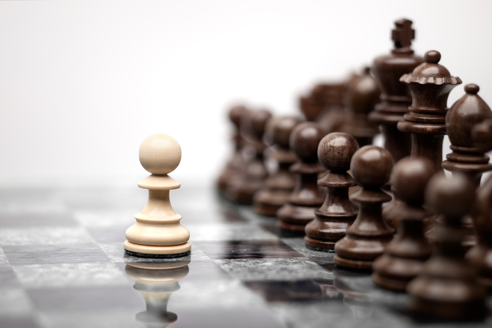 a single pawn faces an army on the chess board illustrating the challenges of new manager training