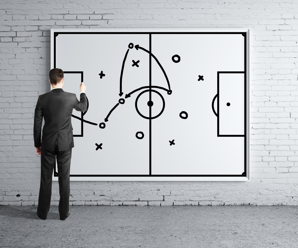 A business man stands at a board where he is drawing a game plan to illustrate strategic clarity