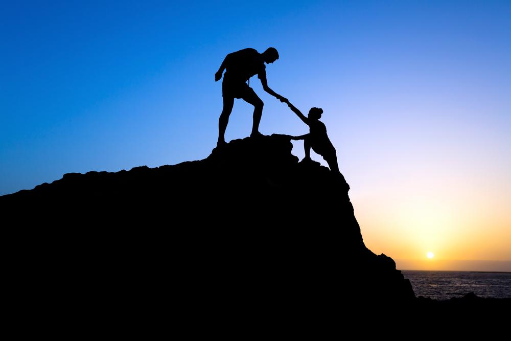 Effective leadership coaching helping hand up mountain