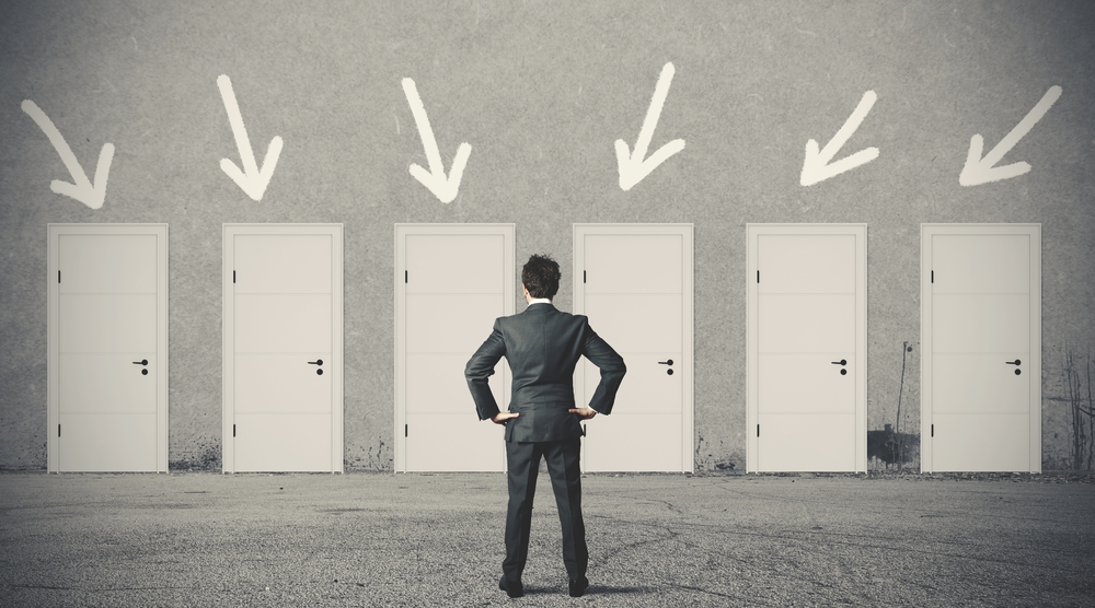 A businessman is looking at 6 doors from which to choose for top talent