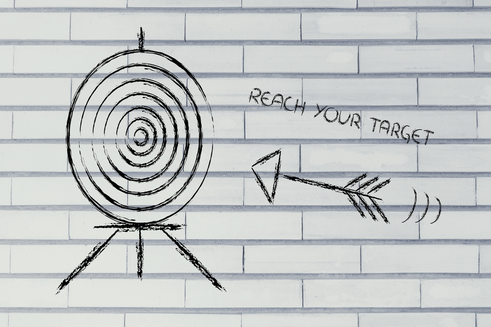 an arrow aimed at a target to show how to Increase the Odds of Reaching Your Goals