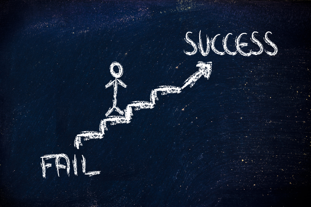 a chalkboard staircase between fail and success as an illustration of why change programs fail