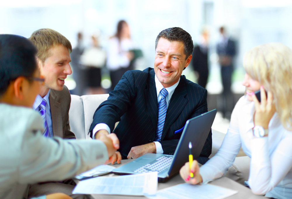 A business shakes hands with his team to illustrate the benefits of gratitude in the workplace