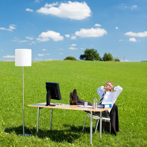 A businessman is relaxing in an open field complacent and showing no Strategic Urgency
