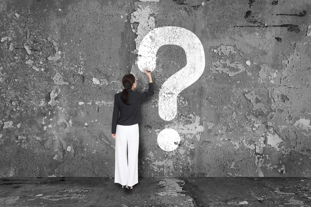 A woman draws a huge question mark on the wall as she ponders Pre-Call Sales Planning Meeting Questions